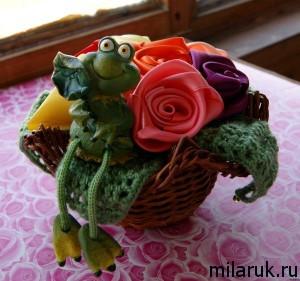 Розы из атласных лент, оформленые в корзинке с салфеткой, связанной крючком и игрушечным лягушонком