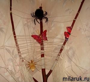Самодельная паутина в углу потолка и покупные пауки и бабочки